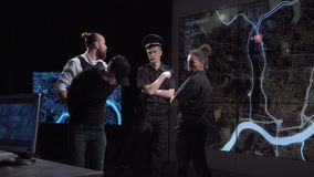 Two police officers watching a digital map. Two proficient police officers analyzing and watching a digital tracking map while a colleague brings a handcuffed stock video footage
