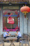 Policeman. Two policemans are watching mobile phone under the window of restaurant in Pingyao, Shanxi, China royalty free stock photos
