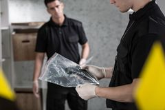 Two policemen collecting evidence Royalty Free Stock Image