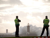 Two policemen watch big wave cover the lighthouse this sunday in oporto. This sunday the second february the portuguese coast was attained by a storm,and in Stock Photography