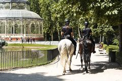 Two policewomen patrolling on horse, in the park. Royalty Free Stock Photos