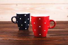 Two polka dots cups. Of coffee with foam standing on wooden table on wooden background royalty free stock images