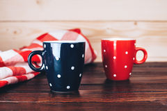 Two polka dots mugs of coffee. Two polka dots cups of coffee with foam standing on wooden table on wooden background with italian checkered tablecloth Stock Images