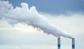 Two polluting chimneys with smoke Stock Image