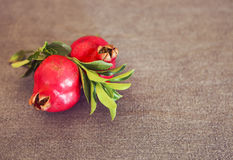Two pomegranate fruits with leaves on textile background Royalty Free Stock Images