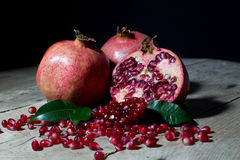 Two Pomegranate and One Half of Pomegranate with Seeds and Green Leaves on Rustic Wooden Table On Black Royalty Free Stock Image