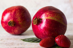 Two pomegranate and strawberries. Fruits on a light background Royalty Free Stock Photography