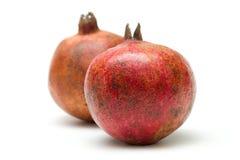 Two pomegranates. Two isolated pomegranates against white background Stock Photos