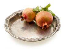 Two pomegranates. Laying on a brilliant tray, on a white background Stock Images