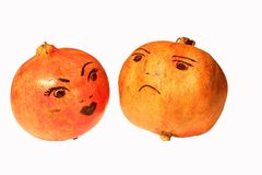 Two pomegranates with painted emotions. Two red ripe pomegranates with painted emotions Stock Photography