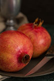Two Pomegranates On A Pewter Plate. Still life close up of two whole red and yellow pomegranates rest on a pewter plate next to a sharp knife.  A pewter goblet Royalty Free Stock Photo