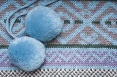 Two pompoms on knitted background Royalty Free Stock Photo