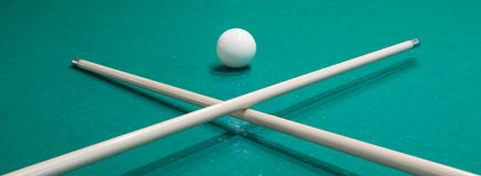 Two pool cues crossed in front of a white ball on a green table royalty free stock photo