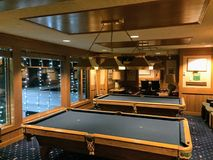 Two pool tables in a fancy club with pristine wood framing royalty free stock photos