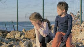 Two poor refugee children boy girl sitting on the stones near the sea. fence barbed wire separating the state. stock footage