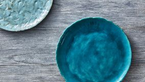 Two porcelain blue bowls on a gray wooden table. Multi-colored ceramic vintage handmade dishes. Top view. Clay handcraft empty blue plates, covered with glazed Stock Photos