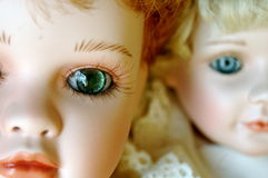 Two Porcelain Dolls with Beautiful Eyes. Closeup of two porcelain dolls, one with a clear , lifelike gaze Stock Image