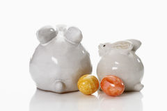 Two porcelain Easter bunny on white background with dyed Easter eggs Royalty Free Stock Photography