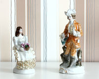 Two porcelain figures on striped background Stock Photos