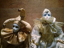 Two porcelain harlequin puppets. On a wooden background Stock Image