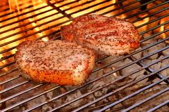 Two Pork Steak Close-up On The BBQ Flaming Grill Stock Photography