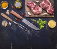 Two pork steak on a cutting board with butter and garlic, border, place for text  on wooden rustic background top view Royalty Free Stock Photo