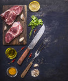 Two pork steak on a cutting board with butter and garlic, vertical, wooden rustic background top view Royalty Free Stock Photo