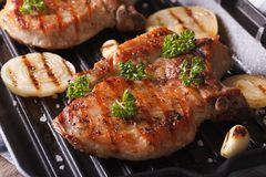 Two pork steak grilled with onions and garlic in a pan grill Stock Image