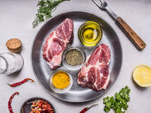 Two pork steaks with oil and spices in a pan with lemon, salt and meat fork wooden rustic background top view close up Stock Image