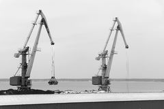 Two port cranes in a coal warehouse Stock Image