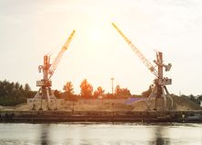 Two port cranes at the riverbank produce river sand, sunset, barge stock image