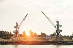Two port cranes at the riverbank produce river sand, sunset, barge stock photography