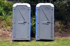 Two portable bathrooms. In the field of a camp ground Royalty Free Stock Image