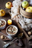 Two portions of apple crumble with almonds on rustic table, whole apples and lighted candle Royalty Free Stock Photo