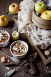 Two portions of apple crumble with almonds on rustic table, whole apples and unlighted candle Stock Images