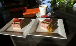 Two portions of a birthday cake. Two portions of a birthday cake served on a white plate accompanied by a cup of coffee stock photos