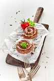 Two portions of coiled grilled beef sausage. From a summer barbecue served on an old vintage wooden board on crumpled paper outdoors on a garden table royalty free stock photography