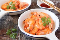 Two portions of fried shrimp and spicy red sauce. On wooden background stock image