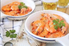 Two portions of fried shrimps and beer. On light background stock images