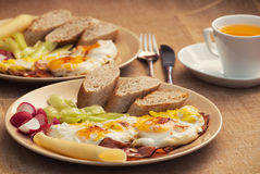 Two portions of ham and eggs with bread, radish, cheese and papr Royalty Free Stock Photos