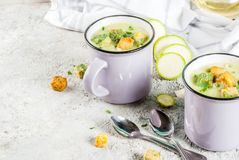Zucchini creamy soup. Two portions of homemade zucchini creamy soup with bread crumbs in mugs on a light concrete background royalty free stock images