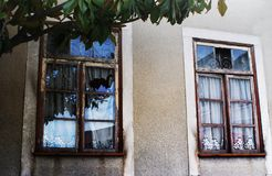 Two Portuguese windows with reflections on the crystals. Two Portuguese windows of an old house; Reflections of the clouds in the crystals and view of some royalty free stock images