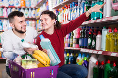 Two positive adult people in good spirits selecting detergents i. Two positive adult people in good spirits selecting detergents оn the shelves in the store Royalty Free Stock Image