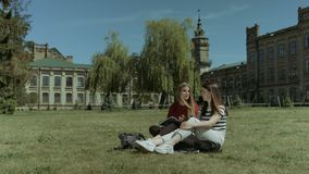 Happy female students relaxing on campus lawn. Two positive attractive female college students chatting and relaxing after study while sitting on campus green stock video