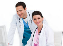 Two positive doctors working at a computer Royalty Free Stock Images