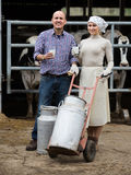 Two positive farmers holding a trolley with milk Stock Photo