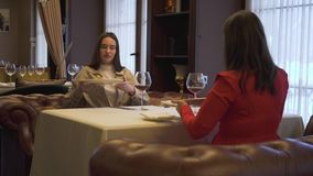 Two positive girlfriends sitting in the modern restaurant, chatting. Women change dishes, give plates to each other. Two positive girlfriends sitting in the stock video footage