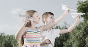 Two positive kids playing with simple paper planes. On sunny day Stock Image