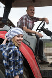 Two positive mechanics opestanding near harvester. In farm Stock Photography