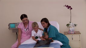 Two positive nurses showing Xray to a little boy. In hospital stock video